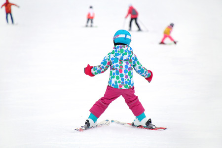 little girl learns to ski in the winter resort