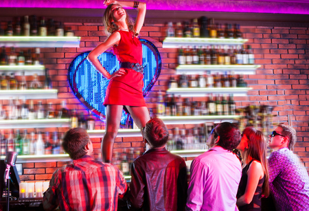 beautiful girl dancing on the bar in a nightclub in the presence of spectators Stock Photo