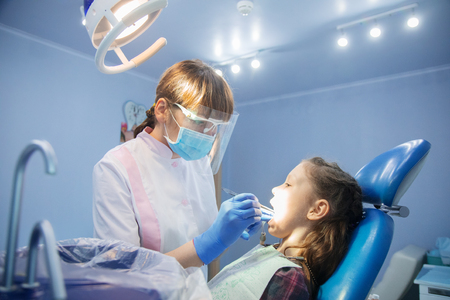 little girl is treating teeth with a pediatric dentist Stock Photo