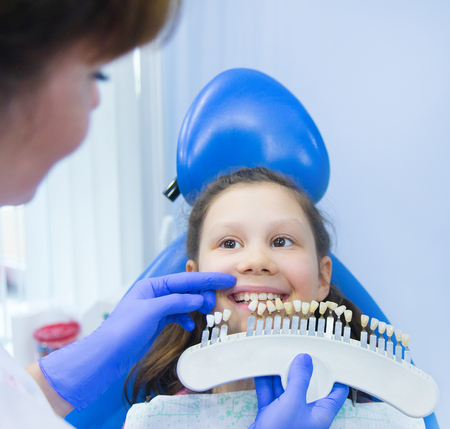 little girl is treating teeth with a pediatric dentist Archivio Fotografico