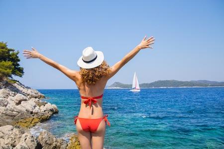 Beautiful young girl in bikini looks at white sailing yacht in the sea