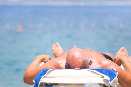 man relaxing in chaise longue on the beach