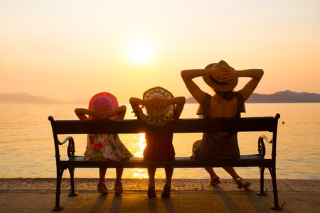 Family with children sitting on a bench on the seafront at sunset in the resort