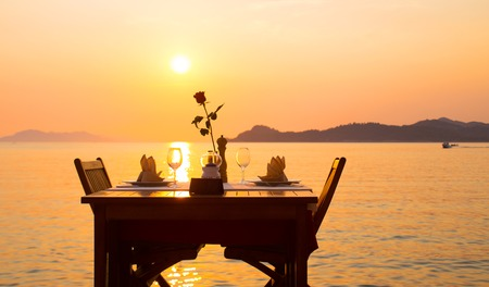 table of a coastal restaurant with a glass of wine and a flower against the backdrop of the sea at sunset Stock Photo