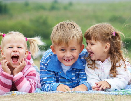 portrait of group laughing children lying on the grass