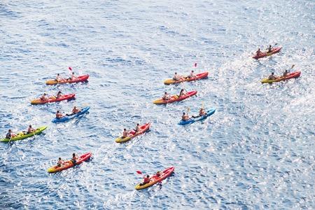 Kayaks. Big group of people kanoeing in the sea. People kayaking in the ocean. Stock Photo