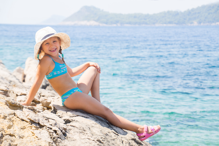 little girl  lying on the beach and sunbathe in the sun
