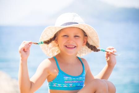 little girl  on the beach and sunbathe in the sun