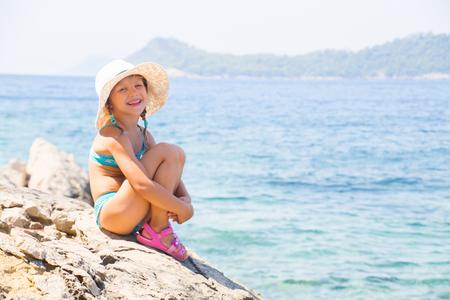 little girl sitting on the beach and sunbathe in the sun