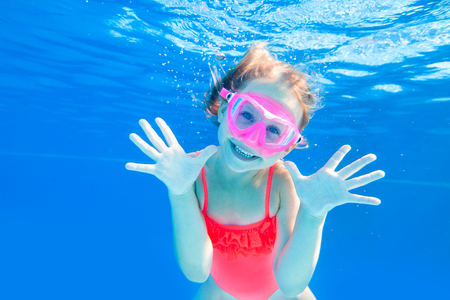 Cheerful little girl playing under  water in pool. Underwater photo. Stock Photo