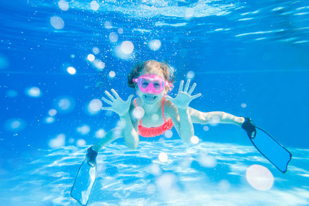 Cheerful little girl playing under  water in pool.Underwater photo.