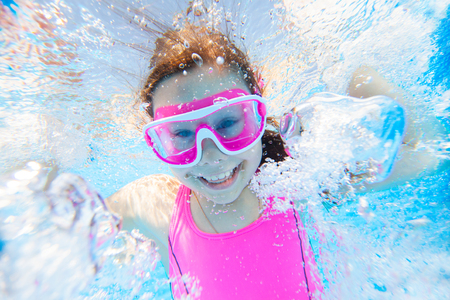 little girl having fun with bubbles in the pooll.Underwater photo.