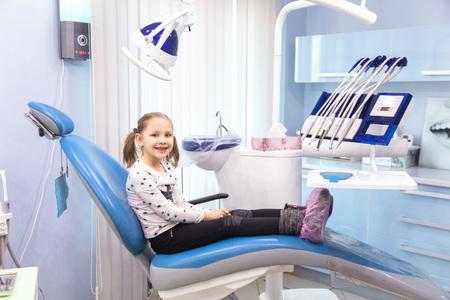 Little girl sitting in a chair near a dentist after dental treatment