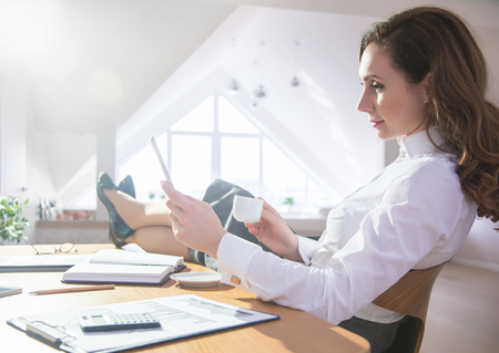 Successful woman with digital tablet in office. Relaxes the legs on the table