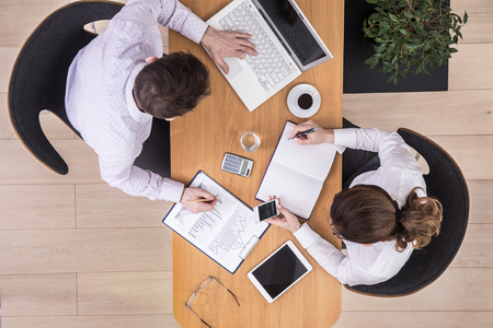 Man and woman, business partners shaking hands at table in office. Top view.