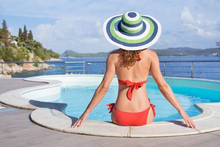 Beautiful young girl in bikini sitting in pool on the shore of  beach of southern sea resort