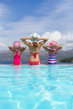 happy family with children sitting on the edge of the pool in a tropical seaside resort against the backdrop of the sea Stock Photo