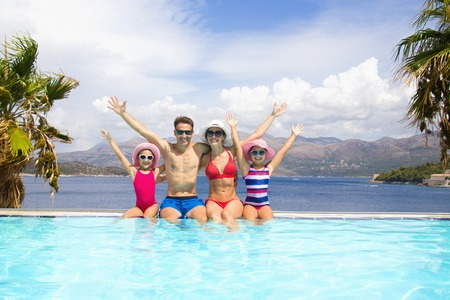 happy family with children sitting on the edge of the pool in a tropical seaside resort against the backdrop of the sea and palms Stock Photo