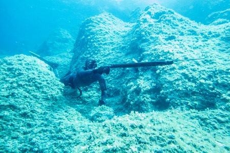 underwater hunter lies at the bottom of the sea with a crossbow in anticipation of a shot at the fish Stock Photo