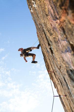 Photo of young man climbing up the rock Standard-Bild