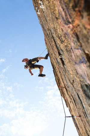 Photo of young man climbing up the rock