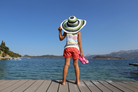 little girl in big hat enjoy on the beach and sunbathe in the sea resort Stock Photo