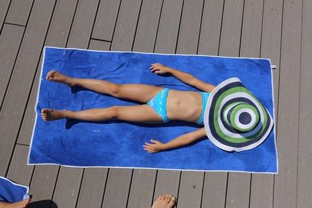 little girl in big hat enjoy on the beach and sunbathe Stock Photo