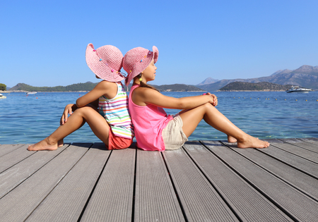 little girls sitting on the beach and sunbathe in the sun Banque d'images
