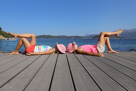 little girls sitting on the beach and sunbathe in the sun Stock Photo