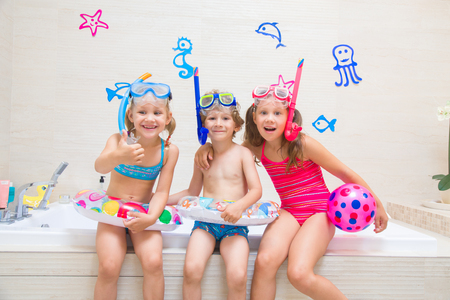Little children in swimsuits and diving  equipmen play in the bathroom like in the sea Stock Photo