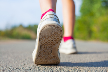 human legs in sneakers are running on a background of road Stock Photo