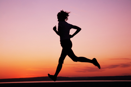 Young Female runner silhouette against the sunset