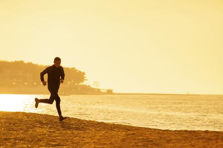 Young man running along the seashore at sunset  Stock Photo