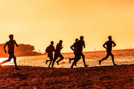 group of young people runs at the beach on beautiful summer sunset Stock Photo