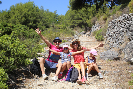 Family with two daughters travels along a beautiful path in the mountains Stock Photo