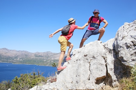 young couple climbing into the mountains on summer vacation Stock Photo