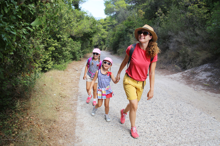 Mom with two daughters travels along a beautiful path in the forest