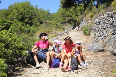 Family with two daughters travels along a beautiful path in the nature park