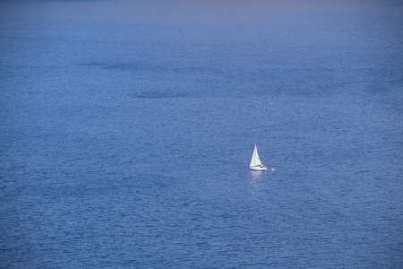 lonely sailing yacht in the middle of the blue sea
