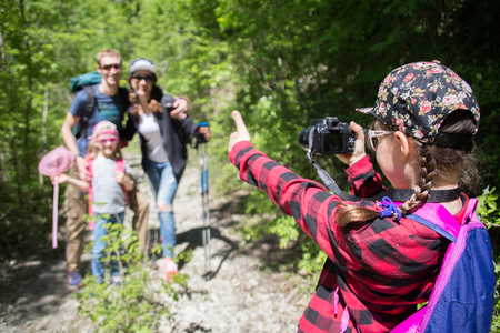 family with two children is photographed on a hike on a path in the forest Stock Photo