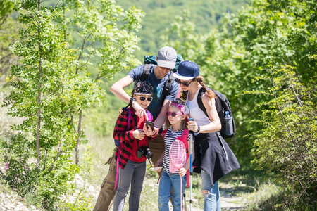 family with two children is guided in a hike through the forest Stock Photo