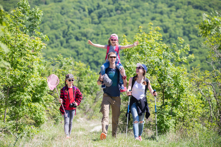Family with two daughters travels along a beautiful path in the forest Stock Photo