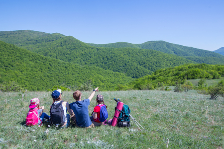 Family with two children resting on a meadow in a hike through mountains Stock Photo