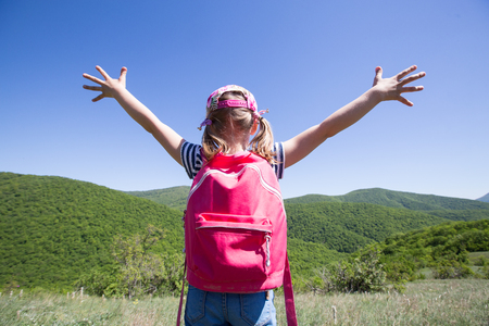 little girl enjoys a beautiful view of a hike through the mountains