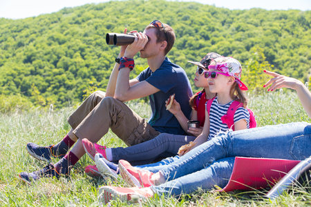 family with two children looks through binoculars on a hike through the mountains