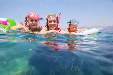 happy family with children is swimming and having fun in the sea on an inflatable mattress.