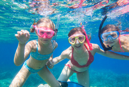 portrait of a mother with two young daughters diving the sea in masks Stock Photo