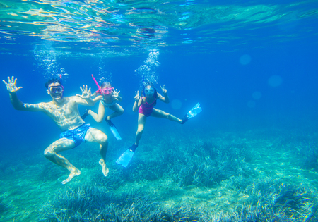 Portrait of a happy dad with two little daughters under water in sea Stock Photo