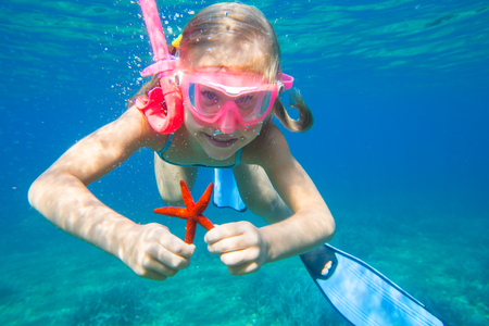 portrait of a little girl diving the sea for a starfish Stock fotó