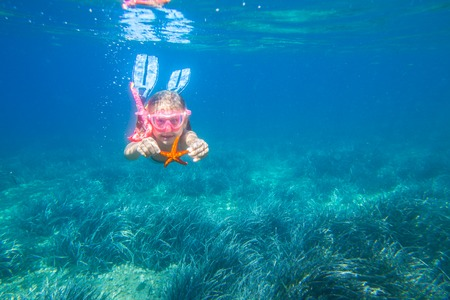 portrait of a little girl diving the sea for a starfish Stock Photo